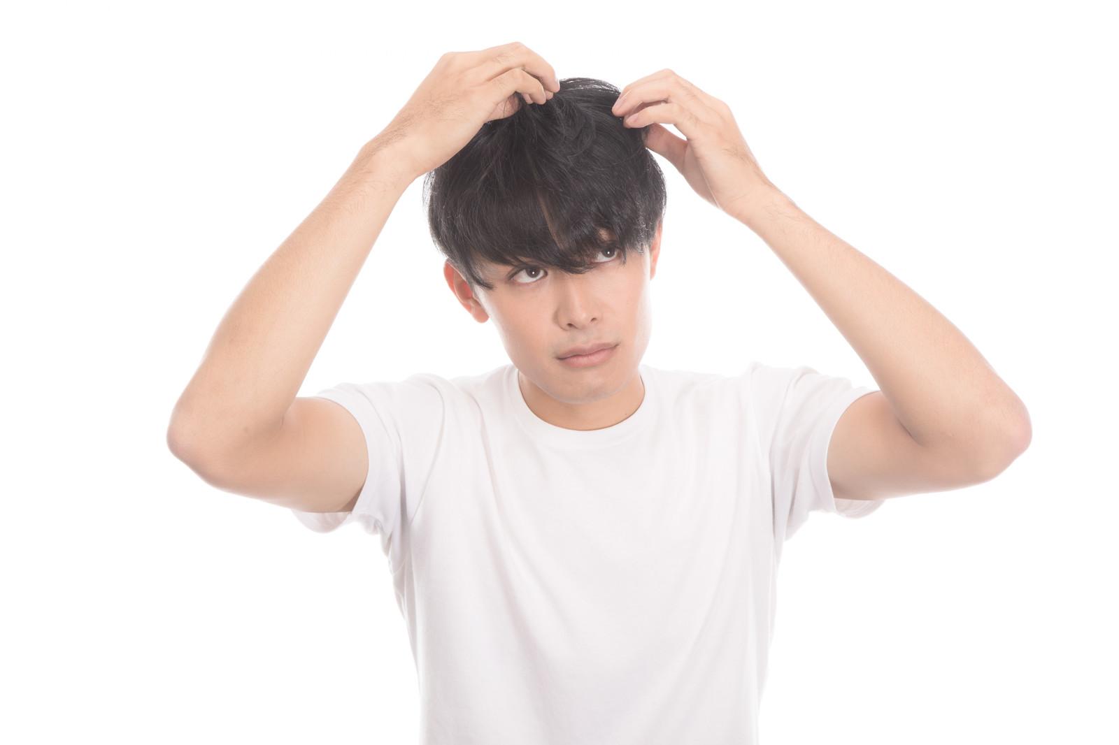 頭髪を気にする若い男